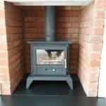 Log burning stove with new brick chamber